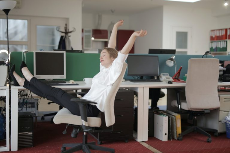 a woman stretching in a chair in her cubicle